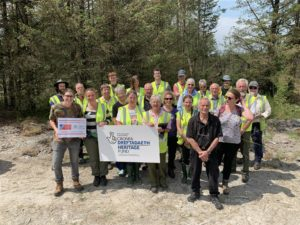 a group of volunteers and staff stand in a group in the forest, holding a National Lottery Heritage Fund sign